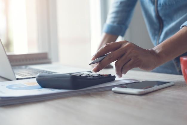 電卓を使用してオフィスでビジネスレポートを計算するビジネスウーマンのクローズアップ