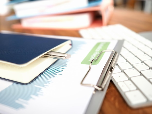 Конец-вверх рабочего места дела с клавиатурой компьютера и финансовыми документами. ежемесячный отчет с графиками по проблемам экономики. блокнот и ручка для заметок. офисная рутина