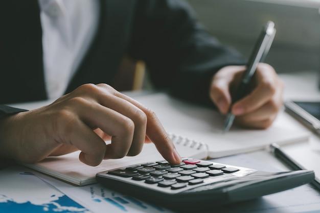 ビジネスマンの会計士や銀行家が計算を行うをクローズアップ。ビジネス金融会計銀行業の概念