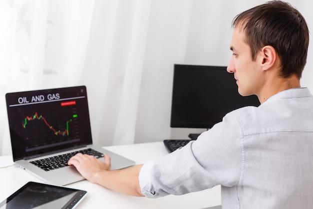 オフィスの職場でラップトップのグラフを分析するビジネスマンのクローズアップ