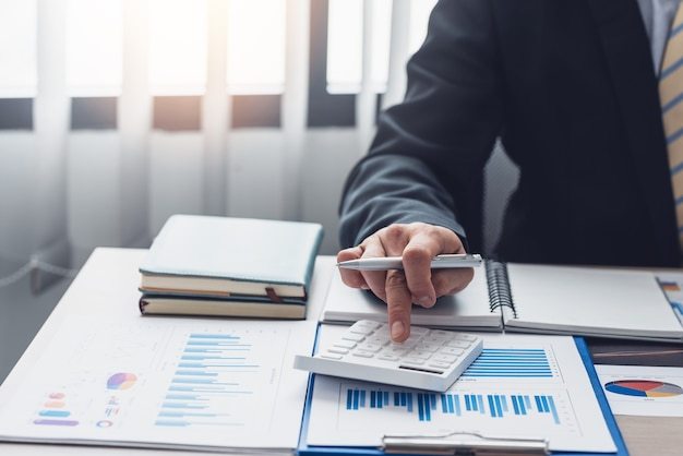 オフィスに配置された計算機計算概念統計グラフでペンを持っているビジネスマンの手のクローズアップ。