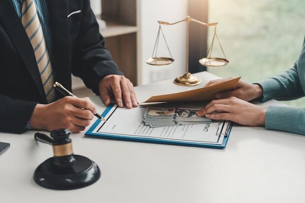 オフィスで契約書と女性の顧客から賄賂を取るビジネスマンの手のクローズアップ。