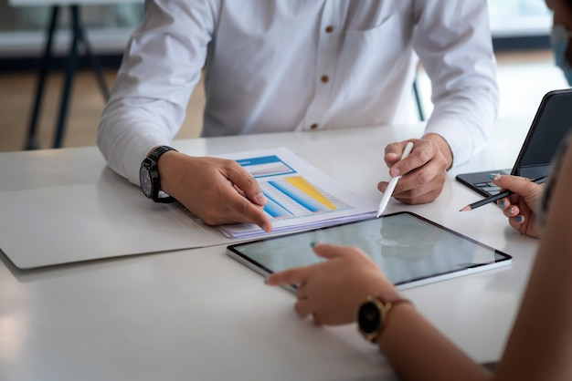 Крупный план рук бизнесмена анализа рабочих обсуждений с помощью офисных документов планшета.