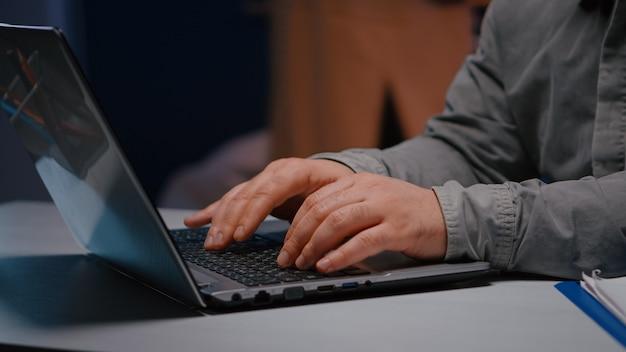 사업가가 인터넷에서 경제 아이디어를 검색하는 신생 기업 사무실의 책상 테이블에 앉아 키보드에 손을 대고 있습니다. 비즈니스 이메일에 응답하는 재무 통계를 입력하는 기업가