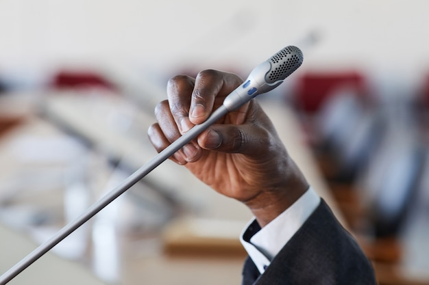 Крупный план бизнесмена, держащего микрофон и говорящего в нем во время конференции