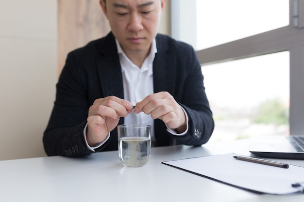 약과 신선한 물 한 잔을 들고 사무실에 있는 사업가의 클로즈업, 두통, 복통 또는 비타민 복용, 건강 관리 개념