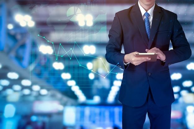 Конец вверх бизнесмена использует таблетку с графиком финансов аналитика