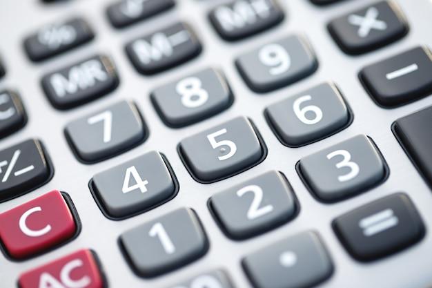 Крупным планом руки бизнесмена или бухгалтера, держащей ручку, работающую на калькуляторе