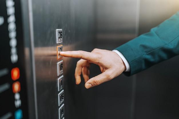 엘리베이터에서 사업가 누르는 버튼 닫습니다.