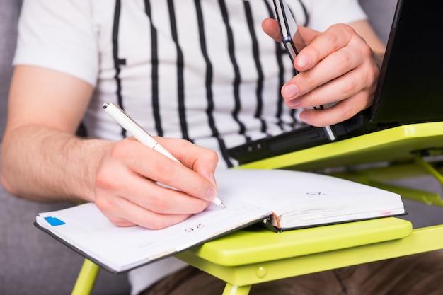 펜과 휴대 전화를 들고 소파에 앉아 집에서 그의 사업을 하는 약속을 작성하는 사업가의 손을 닫습니다