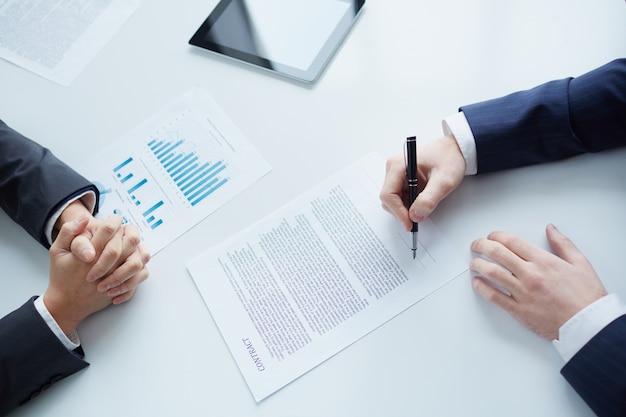 Крупным планом бизнесмен сидит и подписания контракта
