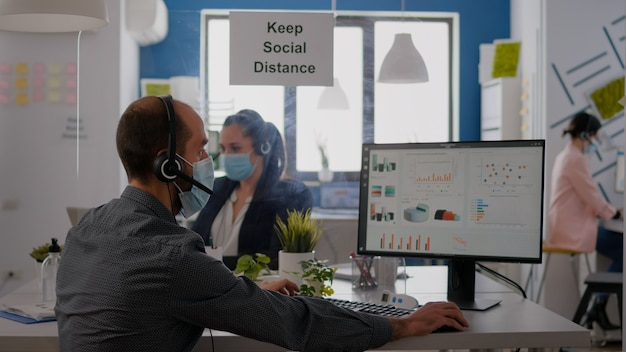 Закройте бизнесмена, говорящего с коллегой в микрофон о деловой встрече в защитной маске. профессиональная команда в масках для предотвращения заражения коронавирусом