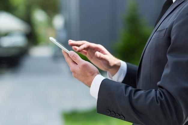 インターネットを閲覧するタブレットを使用してビジネスマンのクローズアップ