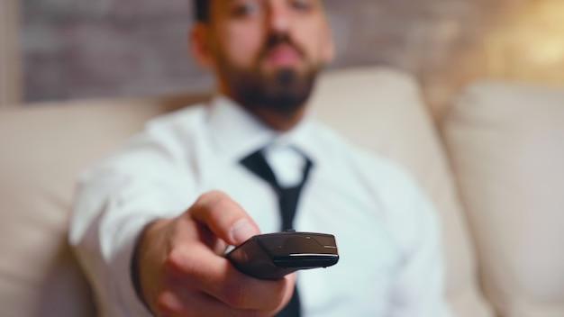 Закройте бизнесмена с помощью пульта дистанционного управления телевизором во время отдыха в гостиной.