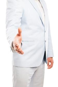 軽いスーツを着ているビジネスマンのクローズアップは、白い背景で隔離の握手に手を伸ばした