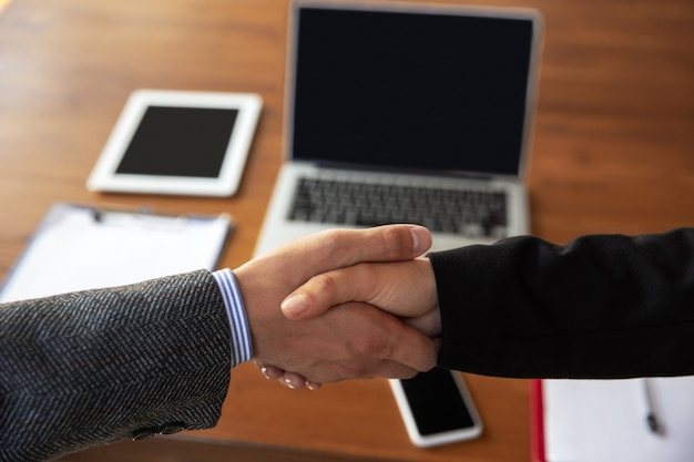 Крупным планом бизнесменов, пожимая руки в конференц-зале