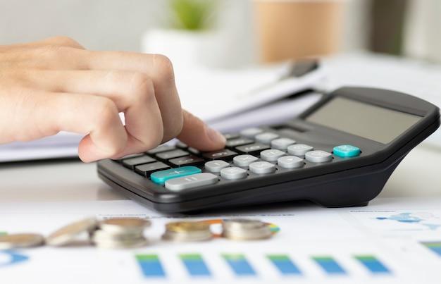 Крупный план бизнесмена, подсчета счетов с калькулятором в офисе