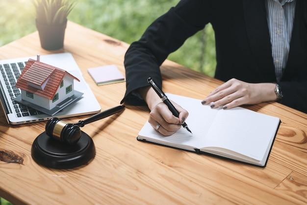 ペンを持って、オフィスの机で木槌ラップトップのサンプル家をメモを取る実業家と弁護士の手のクローズアップ。