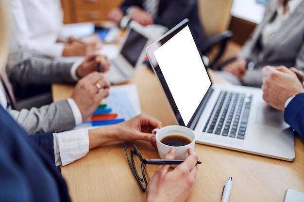会議室の会議室に座っている間一杯のコーヒーを保持している実業家のクローズアップ。