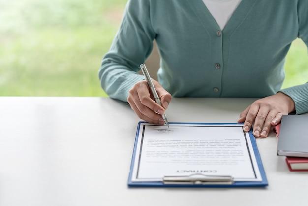 Крупный план бизнес-леди, держащей ручку, подписывающую контракты в офисе.