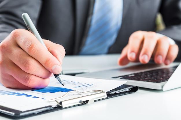 実業家のクローズアップは、ビジネス文書でメモを取ります