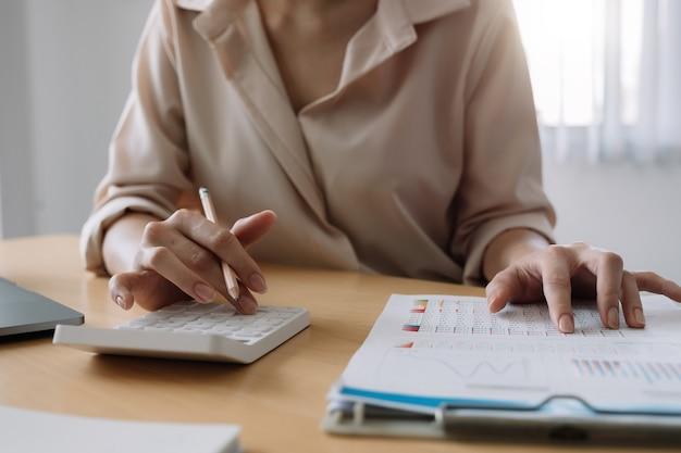 Крупным планом предприниматель или бухгалтер рука держит карандаш и работает на калькуляторе с графиками