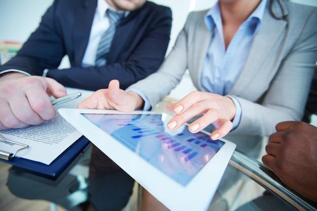 Крупным планом бизнесмен показывает график на цифровой планшет