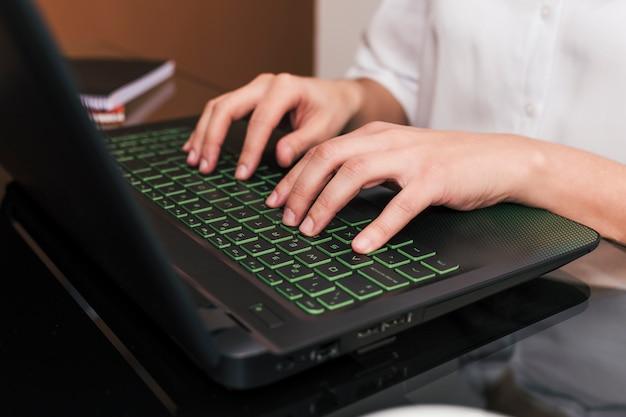 自宅のデスクでラップトップを使用して実業家のクローズアップ。