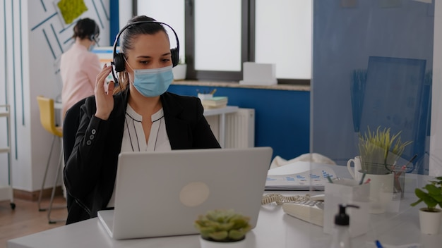 ラップトップコンピューターでマーケティング統計を入力しながらマイクに向かって話しているヘッドセットを身に着けているフェイスマスクで女性実業家のクローズアップ。 covid19パンデミックの間にオフィスの机に座っているフリーランサー