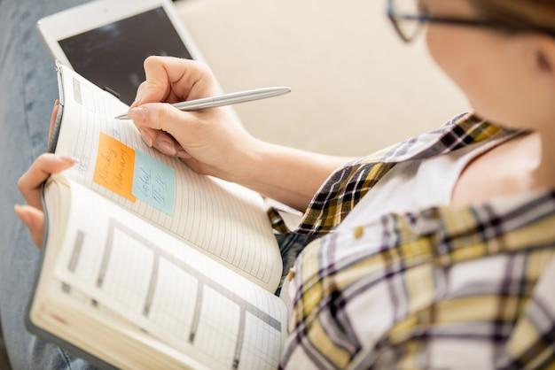 목표를 설정하거나 하루를 계획하는 동안 일기에 메모를 만드는 바쁜 젊은 여자의 근접