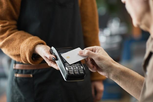 점심을 지불하는 동안 웨이트리스가 들고 있는 단말기에 nfc가 있는 신용 카드를 넣는 카페 고객의 클로즈업