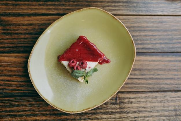 Закройте торт десертный чизкейк с малиновым соусом на тарелке, лежащей на деревенском деревянном столе в кафе-ресторане. вид сверху сверху. концепция образа жизни. скопируйте космическую рекламную площадку.