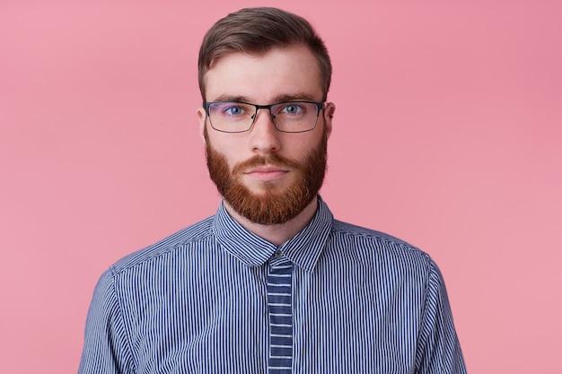 ピンクの背景に分離された感情のないカメラを見て、メガネで穏やかな感情のないひげを生やした若い男のクローズアップ。