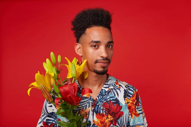 Крупным планом спокойный молодой афроамериканец, одетый в гавайскую рубашку, смотрит в камеру, держит желтые и красные цветы, стоит на красном фоне.