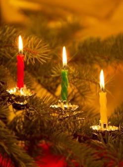 昔ながらのクリスマスツリーに燃えるろうそくのクローズアップ