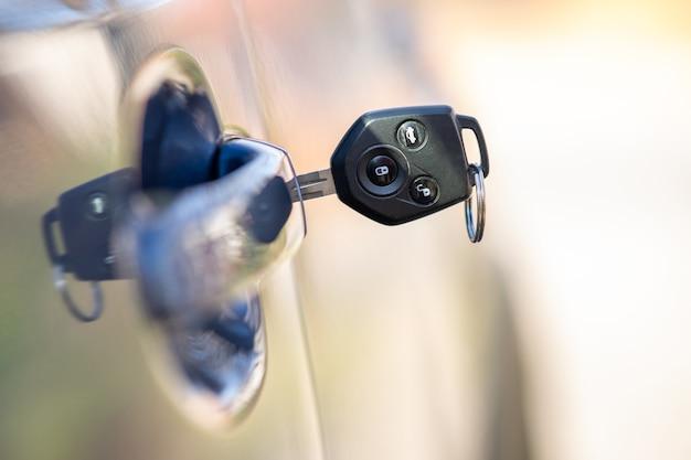자물쇠에서 튀어나온 열쇠로 자동차 문을 닫습니다. 프로세스 열기 또는 닫기 차량의 개념입니다. 프리미엄 사진