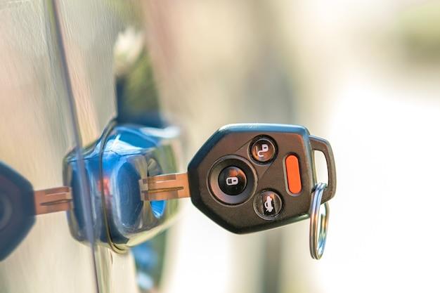 자물쇠에서 튀어나온 열쇠로 자동차 문을 닫습니다. 프로세스 열기 또는 닫기 차량의 개념입니다.
