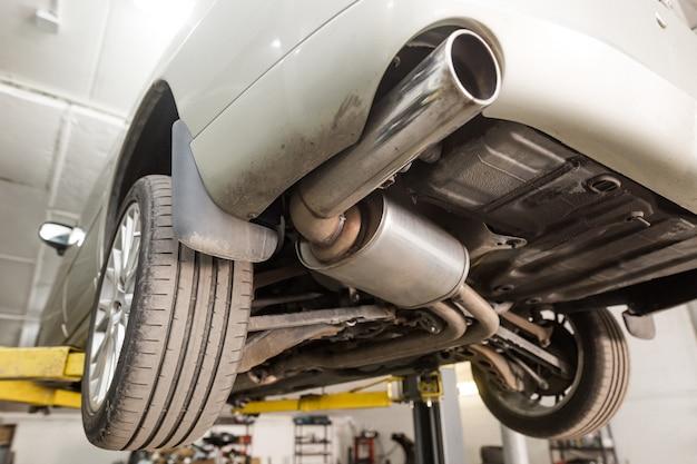 ガレージ、自動車サービスでの自動車排気システムパイプのクローズアップ
