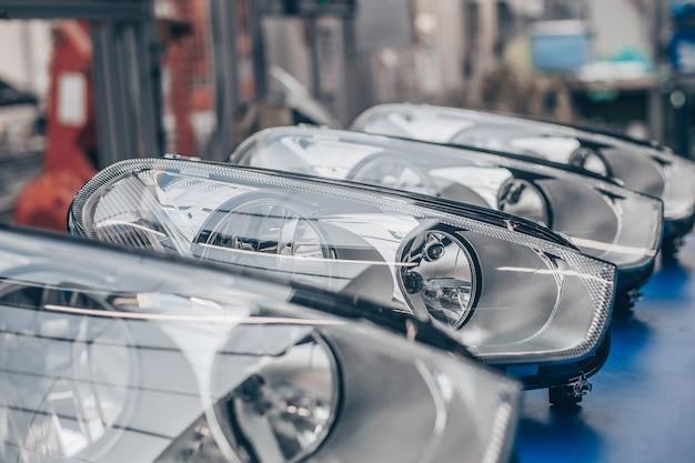 車のヘッドランプ、車に組み立てる準備ができている連続したヘッドライト、自動車産業の概念のクローズアップ