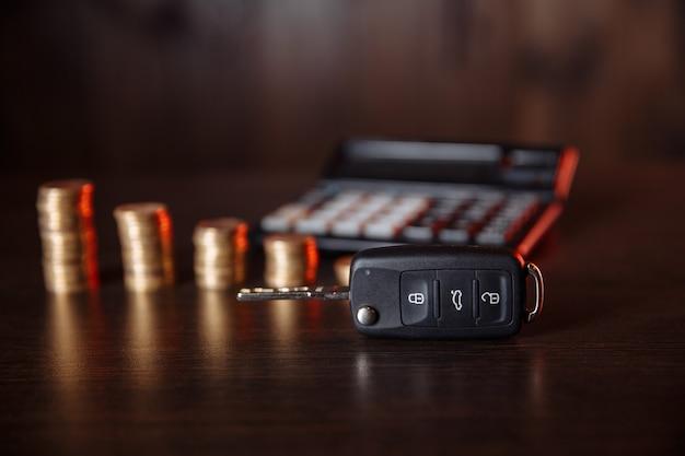 積み上げられたコインと木製のテーブルの電卓の前の車のキーのクローズアップ。お金の節約の概念。