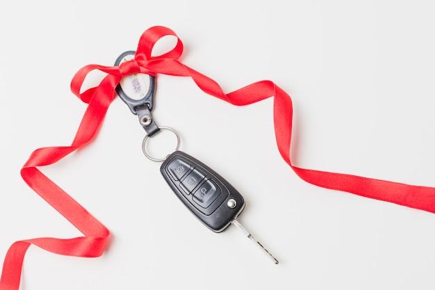 Крупным планом ключи от машины с красным бантом в подарок на белые обои