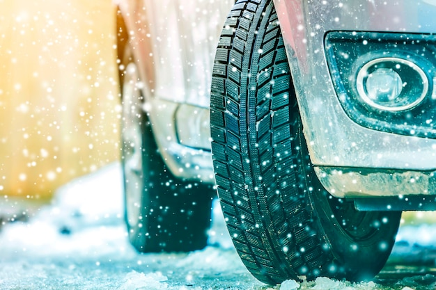 雪道で冬用タイヤの車のホイールのクローズアップ