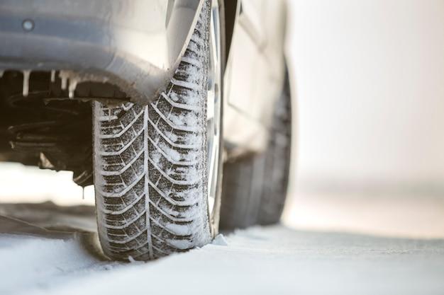 深い雪の中の車の車輪のゴム製タイヤのクローズアップ。輸送と安全の概念。
