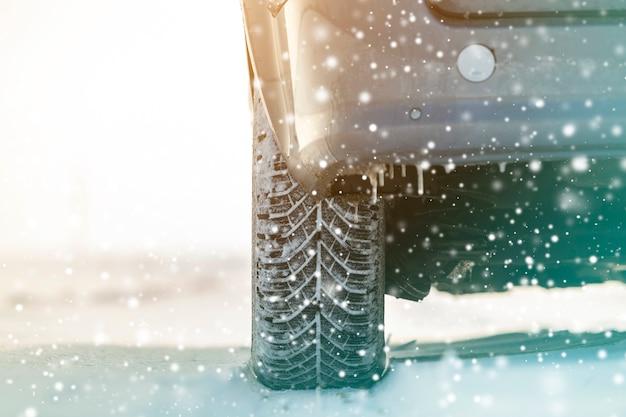 深い冬の雪の中で車のホイールのゴム製タイヤのクローズアップ。輸送と安全のコンセプトです。