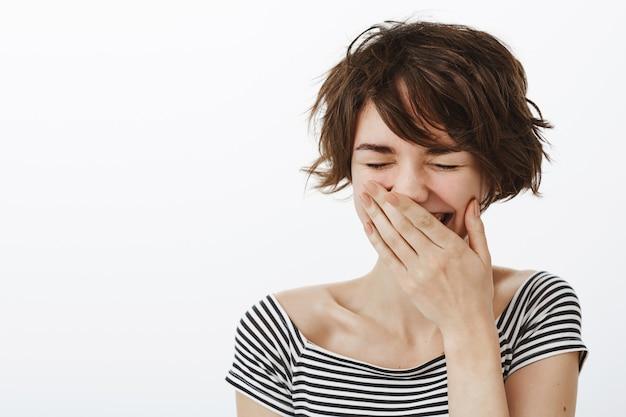 평온한 웃는 여자의 근접 촬영, 손으로 입을 닫고 즐겁게 웃는다.