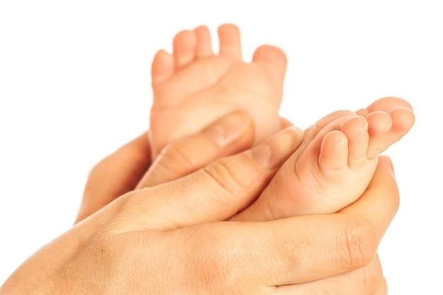 목욕 후 아기의 맨 다리에 마사지를 하는 돌보는 어머니의 손의 클로즈업. 위생 및 자녀의 건강 관리 개념