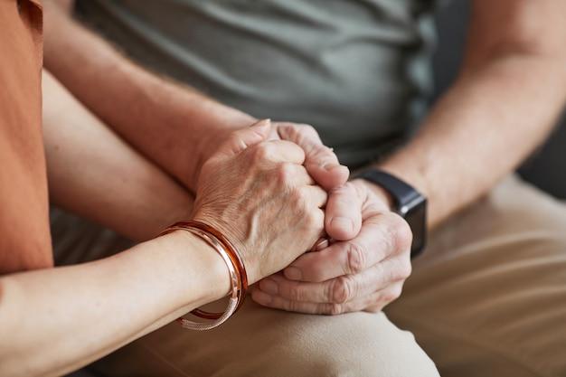 手をつないで、愛を込めてお互いをサポートしている思いやりのある年配のカップルのクローズアップ