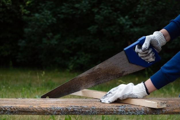 庭で古い鈍いのこぎりで手袋と手のこぎりで木の板を身に着けている大工のクローズアップ。
