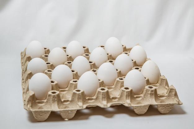 白い背景の上の距離の白い卵とカートンボックスのクローズアップ。検疫ルールの概念