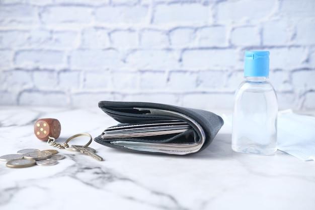 財布の手指消毒剤の鍵とテーブルの上のコインの現金のクローズアップ